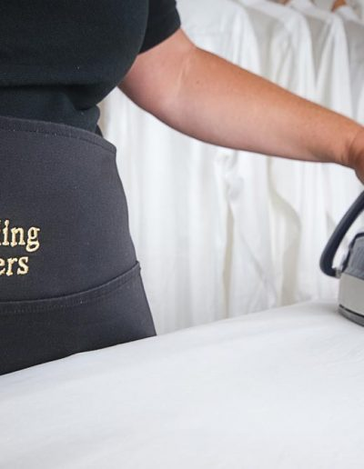 Image of a woman ironing for a cleaning company to illustrate documentary photography for businesses in somerset UK